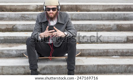 Young man using his smartphone for listening to music. - stock photo