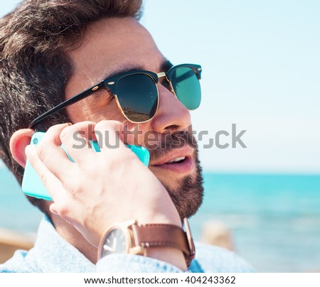 young man using his telephone in the beach