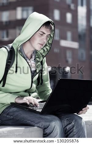 Young man using laptop - stock photo