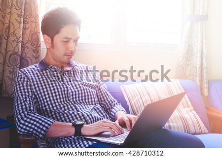 Young man using laptop for his business, working, browsing or even study at his house. People lifestyle - stock photo