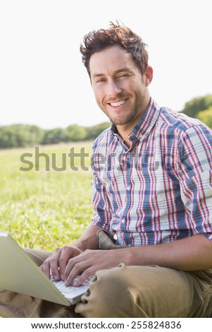 Young man using laptop in the countryside on a sunny day - stock photo