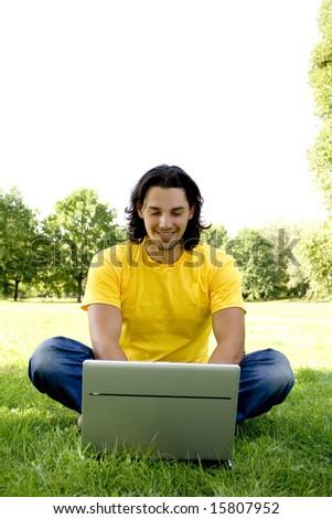 Young man using laptop outdoors - stock photo