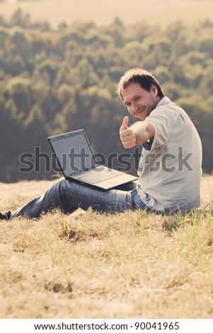 young man using laptop sitting on the grass on the hillside - stock photo