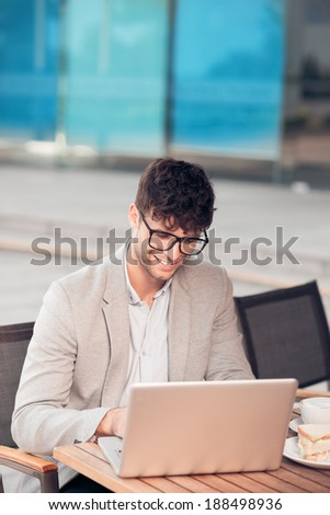 Young man using laptop while sitting in the cafe - stock photo