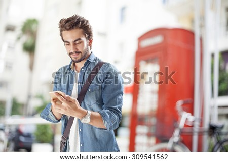 Young man using mobile phone in street - stock photo