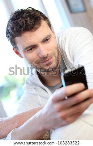 Young man using mobile phone to send short message - stock photo