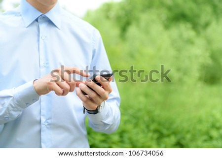Young man using mobile smart phone in the park. - stock photo