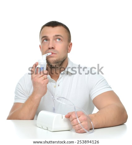 Young man using nebulizer for respiratory inhaler Asthma Treatment isolated on a white background - stock photo