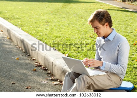 Young man using phone and laptop outdoors