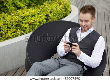 Young man using phone. Outdoors photo.