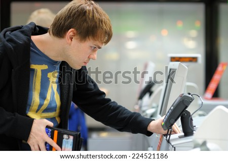 Young man using pos terminal at the shop (paying credit card for purchases)