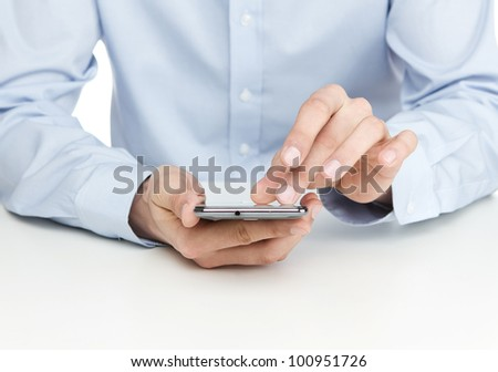 Young man using smart phone by the desk - stock photo