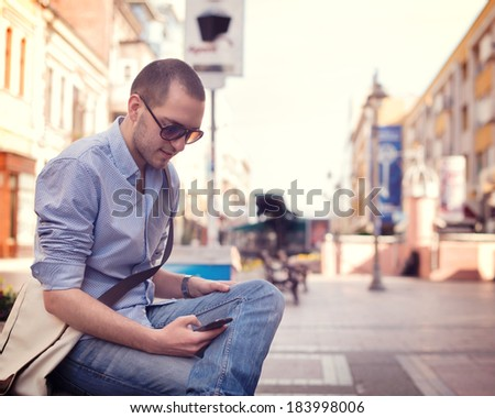 Young man using smart phone on the street - stock photo