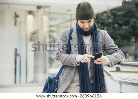 young man using smartphone in the city - stock photo