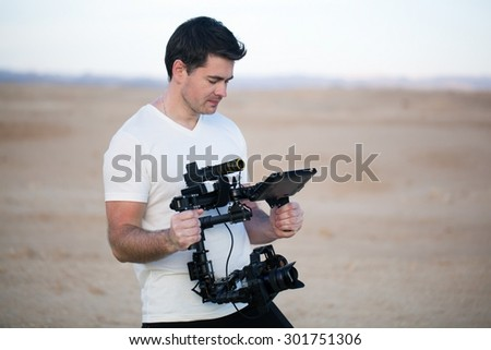 Young man using steadycam for shooting on beach - stock photo