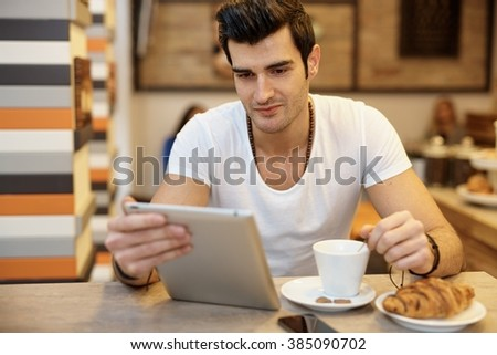 Young man using tablet computer in cafeteria. - stock photo