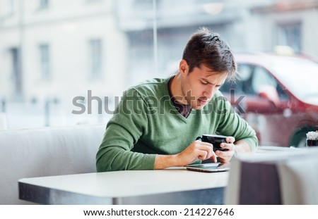 Young man using tablet computer in coffee shop - stock photo