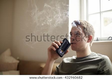 Young Man Using Vapourizer As Smoking Alternative - stock photo