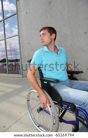 Young man using wheelchair in town - stock photo