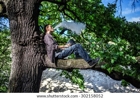 Young man vaping electronic cigarette and sitting on the tree. Daylight summer shot. - stock photo