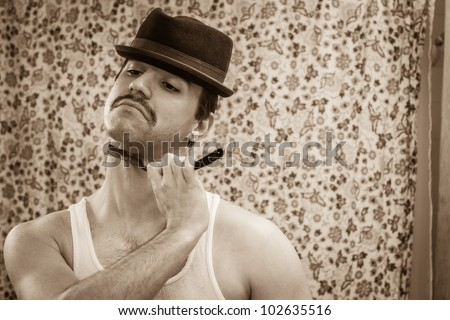 Young man, vintage sepia color, shaving neck in bathroom mirror with old straight razor, reflection, wearing wife beater, hat, shower curtain behind