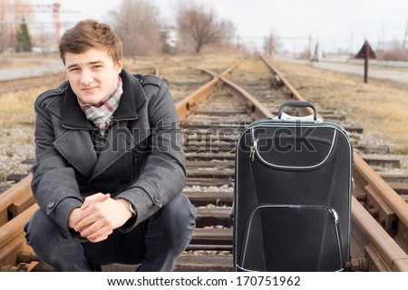 Young man waiting at a rural siding for a train sitting on the wooden sleepers in the centre of the track with his suitcase staring down the line - stock photo