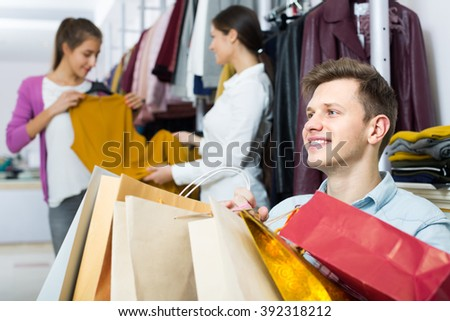 Young man waiting for his girlfriend choosing new dress at the shop