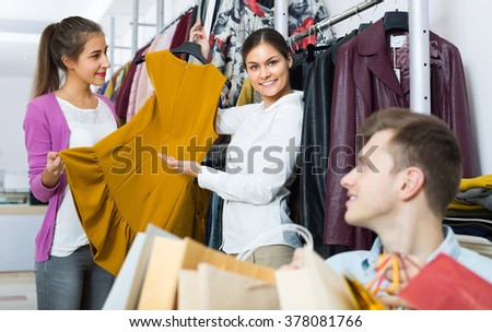 Young man waiting for his smiling girlfriend choosing new dress at the shop  - stock photo