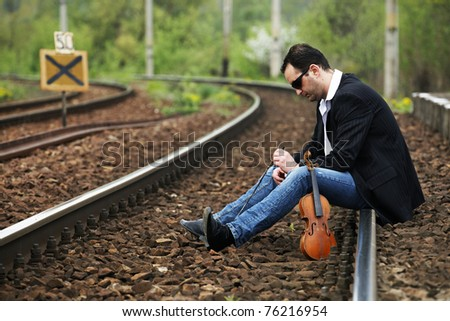Young man waiting for the train - stock photo