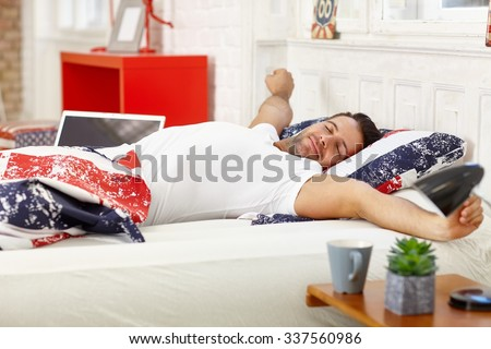 Young man waking up in the morning, stretching in bed. - stock photo