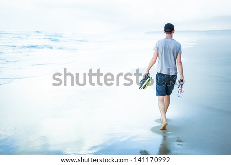 young man walking at sea shore alone and relaxed - stock photo