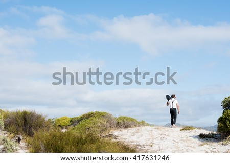 Young man walking barefoot on white sand. Rear view of young man walking and holding vintage radio. Man listening to music while walking during daytime. - stock photo