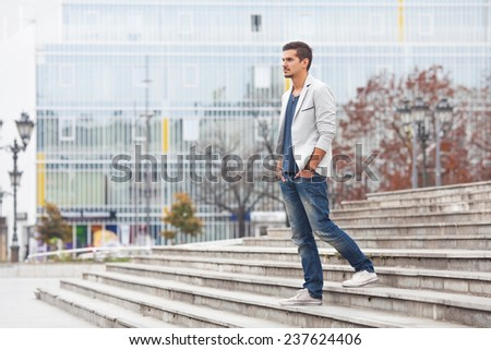 Young man walking down the stairs - stock photo