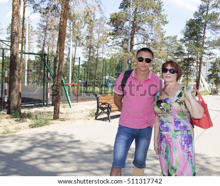 Young man walking in the park with her mother