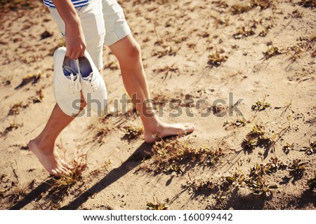 Young man walking in warm summer beach alone with his shoes in hand and having fun. - stock photo