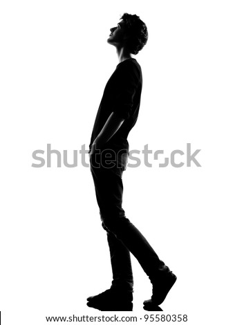 young man  walking looking up silhouette in studio isolated on white background
