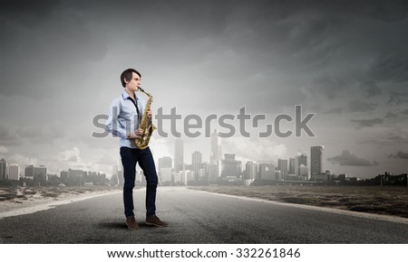 Young man walking on road playing saxophone