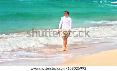 Young Man walking on the Beach Seaside sand with blue Sea on background Summer Travelling Tropical island