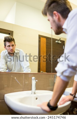 Young man washing face in bathroom