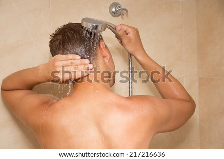 young man washing his head in shower - stock photo
