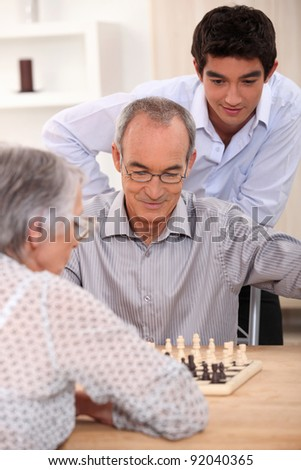 Young man watching an older couple play chess