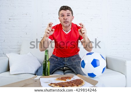 young man watching football game on television nervous and excited suffering stress fingers crossed for goal on sofa couch at home with ball , beer bottle and  pizza looking crazy anxious - stock photo