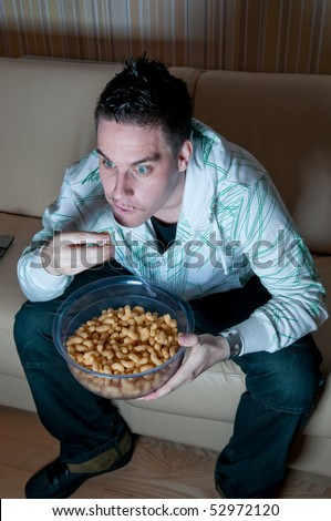 Young man watching television and eating snacks