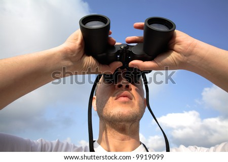 Young man watching thru binoculars
