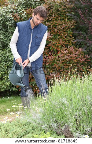 young man watering plants - stock photo