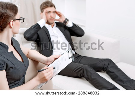 Young man wearing a black suit lying on a couch telling his problems and holding hands near head, psychologist with clipboard listening to him and making notes during therapy session, selective focus - stock photo