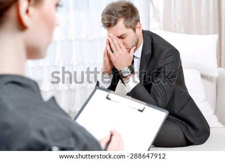 Young man wearing a black suit sitting on a couch hiding his face with his hands, psychologist with clipboard listening to him and making notes during therapy session, selective focus - stock photo