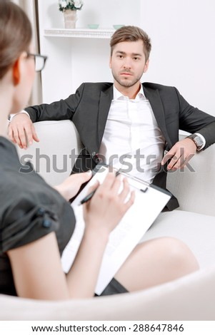 Young man wearing a black suit sitting on a couch looking at his doctor and listening, psychologist with clipboard talking to him and making notes during therapy session, selective focus - stock photo