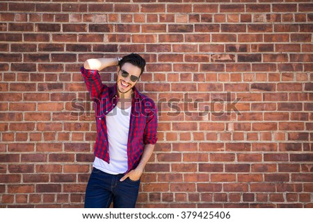 Young man wearing a check shirt and jeans against a brick wall - stock photo