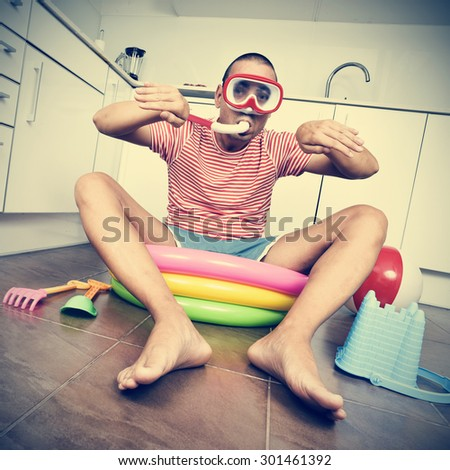 young man wearing a diving mask and a snorkel pretending he is swimming into an inflatable water pool, placed in the kitchen, with a dramatic effect - stock photo